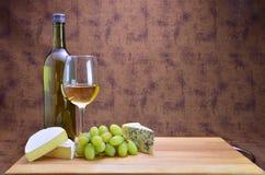 Vinho branco, uvas e queijo Fotos de Stock