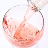 Vinho cor-de-rosa que está sendo derramado Fotografia de Stock