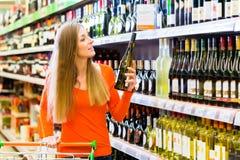 Vinho de compra da mulher no supermercado Fotografia de Stock