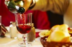 Vinho de derramamento com jantar Fotografia de Stock