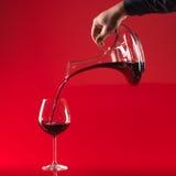 Vinho de derramamento da mão no vidro do decater Imagem de Stock Royalty Free
