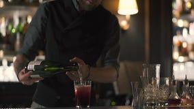 Vinho de derramamento do barman farpado alto no vidro com gelo Empregado de bar que faz o cocktail na posição moderna da barra pe video estoque