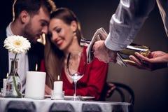 vinho de derramamento do garçom quando pares bonitos que têm a data romântica no restaurante imagem de stock royalty free