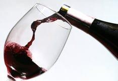 Vinho de derramamento em um vidro Imagens de Stock
