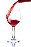 Vinho de Ed que derrama no vidro isolado Imagens de Stock Royalty Free