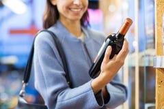 Vinho de escolha e de compra da mulher feliz no mercado Imagem de Stock