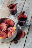 Vinho e especiarias ferventados com especiarias no fundo de madeira Fotografia de Stock