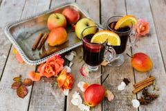 Vinho e especiarias ferventados com especiarias no fundo de madeira Imagem de Stock