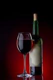Vinho e vidro contra um fundo preto com luz vermelha Foto de Stock