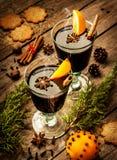 Vinho ferventado com especiarias com fatias alaranjadas na madeira - bebida de aquecimento do inverno Imagens de Stock