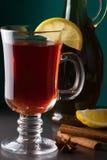 Vinho ferventado com especiarias com limão em um fundo escuro Imagem de Stock Royalty Free