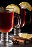 Vinho ferventado com especiarias com limão em um fundo escuro Foto de Stock