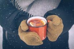 Vinho ferventado com especiarias em um copo vermelho em mitenes das mãos das mulheres Bebida quente do inverno exterior no fundo  fotografia de stock