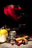 Vinho ferventado com especiarias em um fundo preto Fotografia de Stock