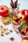 vinho ferventado com especiarias em vidros em um fundo claro, Apple da rede de pesca, canela, vinho Fotos de Stock Royalty Free