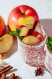 vinho ferventado com especiarias em vidros em um fundo claro, Apple da rede de pesca, canela, vinho Imagens de Stock