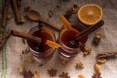 Vinho ferventado com especiarias na juta nos vidros Fotografia de Stock