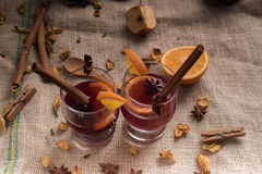 Vinho ferventado com especiarias na juta nos vidros Fotografia de Stock Royalty Free