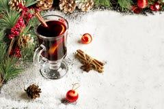 Vinho ferventado com especiarias na neve Foto de Stock