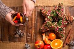 Vinho ferventado com especiarias nas mãos, em especiarias e em ingredientes fêmeas do fruto na tabela de madeira Bebida de aqueci Fotografia de Stock Royalty Free
