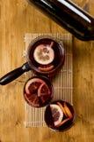 Vinho ferventado com especiarias nos vidros com a garrafa no fundo de madeira, vista superior imagens de stock