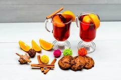 Vinho ferventado com especiarias perto das fatias de laranja Bebida ou bebida com laranja e canela Conceito alcoólico do cocktail foto de stock