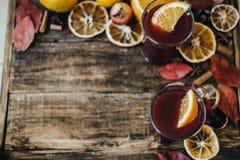 Vinho ferventado com especiarias quente com fatias alaranjadas secas na placa de madeira Christma Imagem de Stock Royalty Free