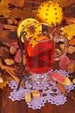 Vinho, laranjas, porcas e doces ferventados com especiarias nas folhas de outono do fundo Foto de Stock