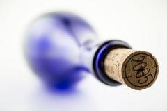 Vinho azul da garrafa com uma cortiça isolada no CCB branco imagens de stock royalty free