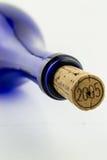 Vinho azul da garrafa com uma cortiça isolada no CCB branco foto de stock