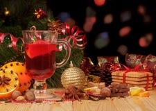 Vinho, árvore de Natal, porcas e doces ferventados com especiarias no preto abstrato Fotografia de Stock