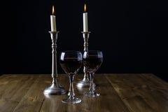 Vinho tinto com velas na tabela de madeira Imagem de Stock