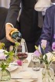 Vinho tinto de derramamento da garrafa no vidro na tabela do partido decorada com flores bonitas fotografia de stock
