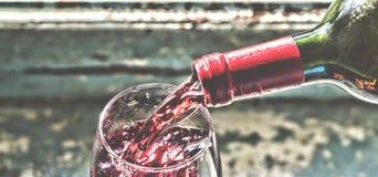 Vinho tinto de derramamento do vinho em um vidro Fotografia de Stock