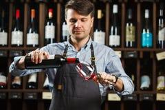 Vinho tinto de derramamento do sommelier masculino em copos de vinho longo-provindos Fotos de Stock Royalty Free