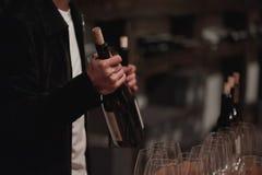 Vinho tinto de derramamento do sommelier masculino em copos de vinho longo-provindos Fotos de Stock