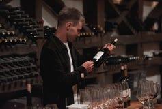 Vinho tinto de derramamento do sommelier masculino em copos de vinho longo-provindos Imagens de Stock