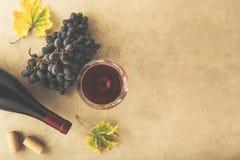 Vinho tinto em um vidro, em uvas, em garrafa e em cortiça na tabela imagem de stock