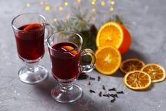 Vinho tinto ferventado com especiarias com especiarias e laranja no fundo escuro Bebida de aquecimento imagem de stock royalty free