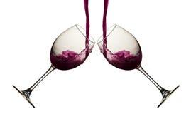 Vinho tinto que derrama em dois copos de vinho no branco Imagem de Stock