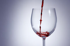 Vinho tinto que derrama em um vidro com o a com fundo Imagem de Stock Royalty Free