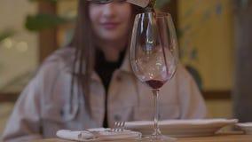 Vinho tinto que derrama lentamente no vidro no fim do primeiro plano acima A jovem mulher está no fundo Movimento lento video estoque