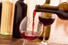 Vinho tinto que derrama no vidro, close-up Imagem de Stock Royalty Free
