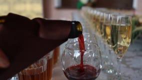 Vinho tinto que derrama no vidro de vinho, close-up filme