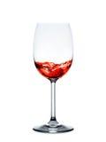 Vinho tinto que derrama no vidro de vinho isolado no fundo branco Imagem de Stock
