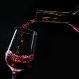 Vinho tinto que derrama no vidro de vinho isolado no preto Foto de Stock Royalty Free