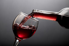 Vinho tinto que derrama no vidro no preto Foto de Stock Royalty Free