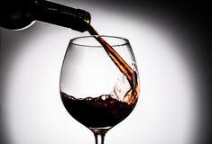 Vinho tinto que está sendo derramado da garrafa no vidro de vinho Imagens de Stock