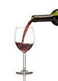 Vinho tinto que está sendo derramado no vidro de vinho Fotografia de Stock Royalty Free