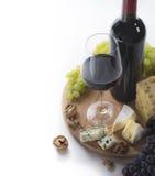 Vinho tinto, vidro, uvas, queijo e porcas Fotografia de Stock Royalty Free